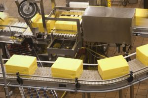 Conveyor belt carrying blocks of cheese to a slicer at a food processing center. Image is slightly grainy with some motion blur.Click below for my other food factory images: